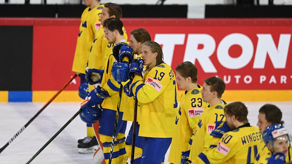 Besvikna svenska ishockeyspelare står på isen.
