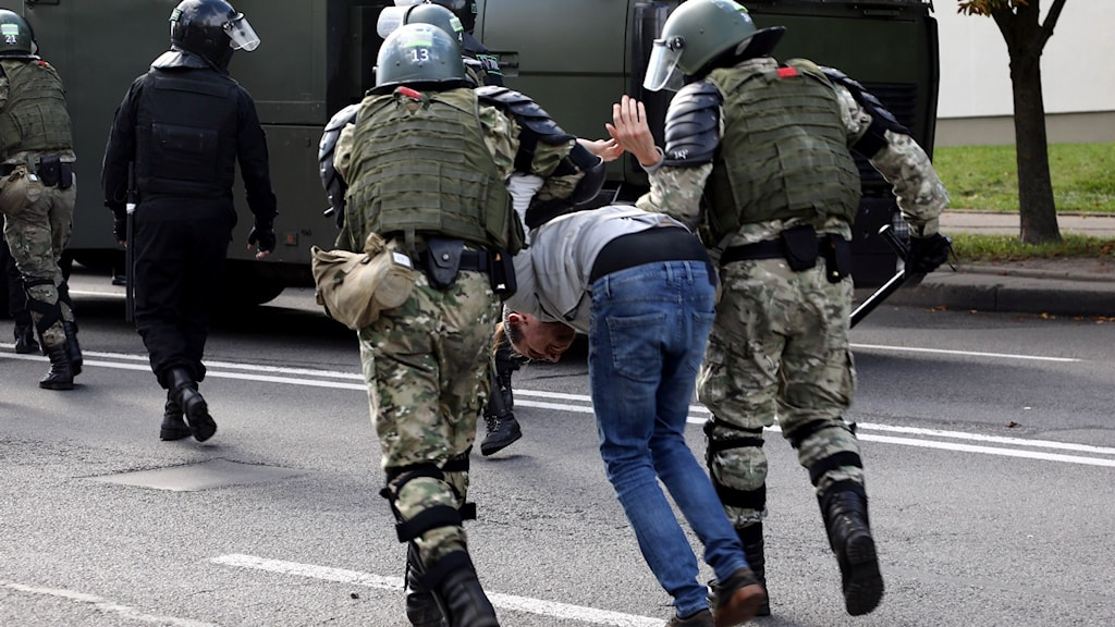 Militären griper en man under protester i Minsk.