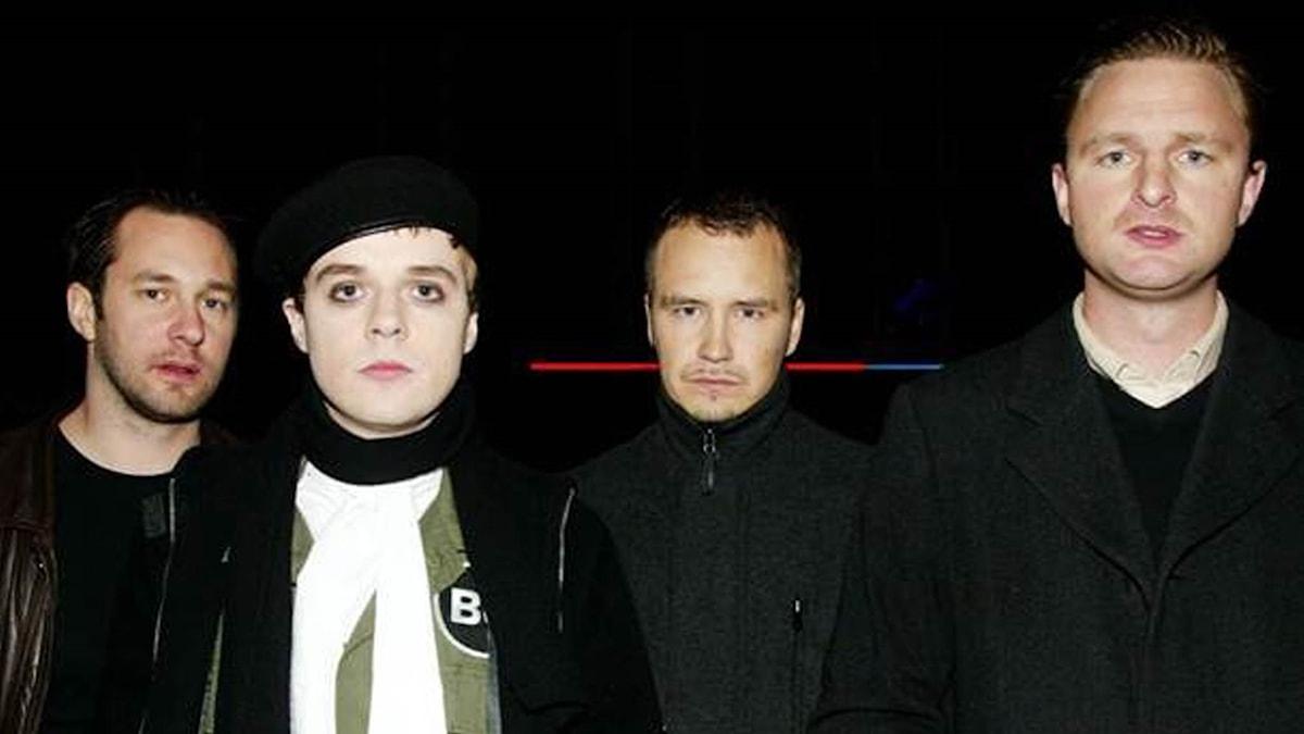 Bandbilder tagen på natten med de fyra svartklädda bandmedlemmarnas ansikten i fokus.