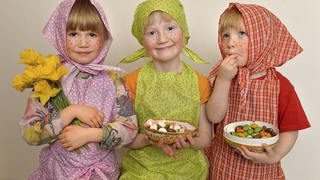 På fotot syns tre tjejer som har klätt ut sig till påskkärringar. De har godis i påskägg.