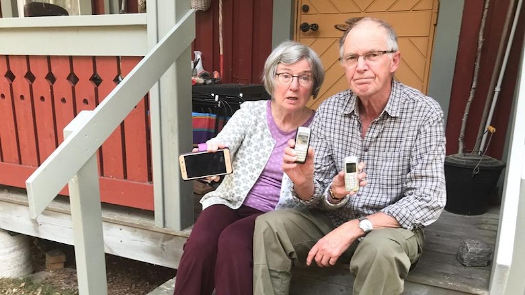 Bilden visar två äldre personer på trappen till sitt hem. De håller upp mobiltelefoner som är av.