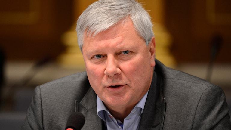 På fotot är Lars Ohly klädd i en grå kavaj och en blå skjorta. Han har ingen slips.