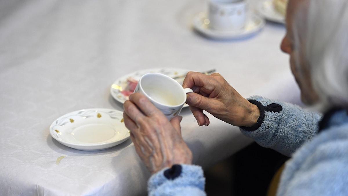 På fotot ser man en äldre kvinna som dricker kaffe. Man ser inte hennes ansikte.