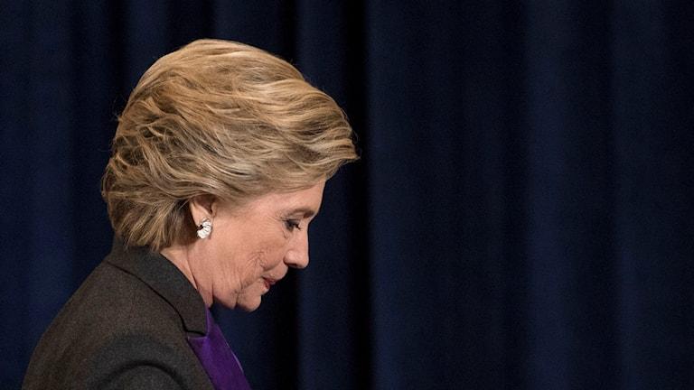 Hillary Clinton går med nedböjt huvud.