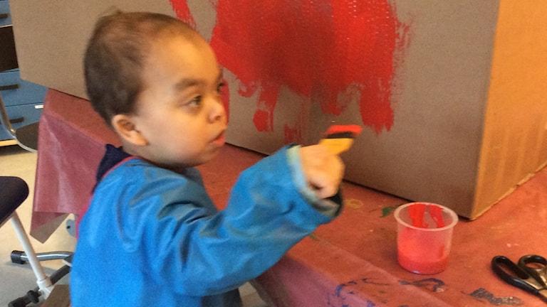 På fotot ser man erik som målar en kartong.
