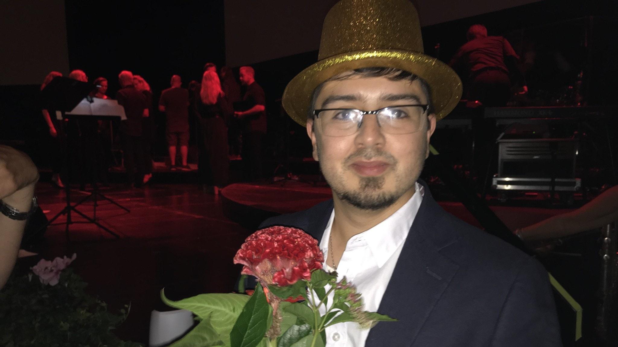 Fotot visar en man i en guldhatt och glasögon som håller i en röd blomma.