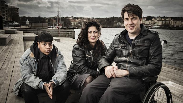 Alla tre har mörkt hår. Jonas sitter i en rullstol.