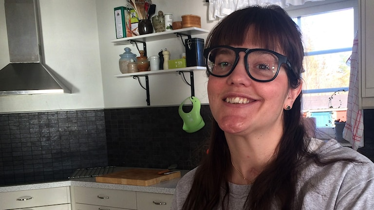 Porträtt på Anna Holmlund när hon sitter i ett kök och ler och tittar rakt in i kameran.