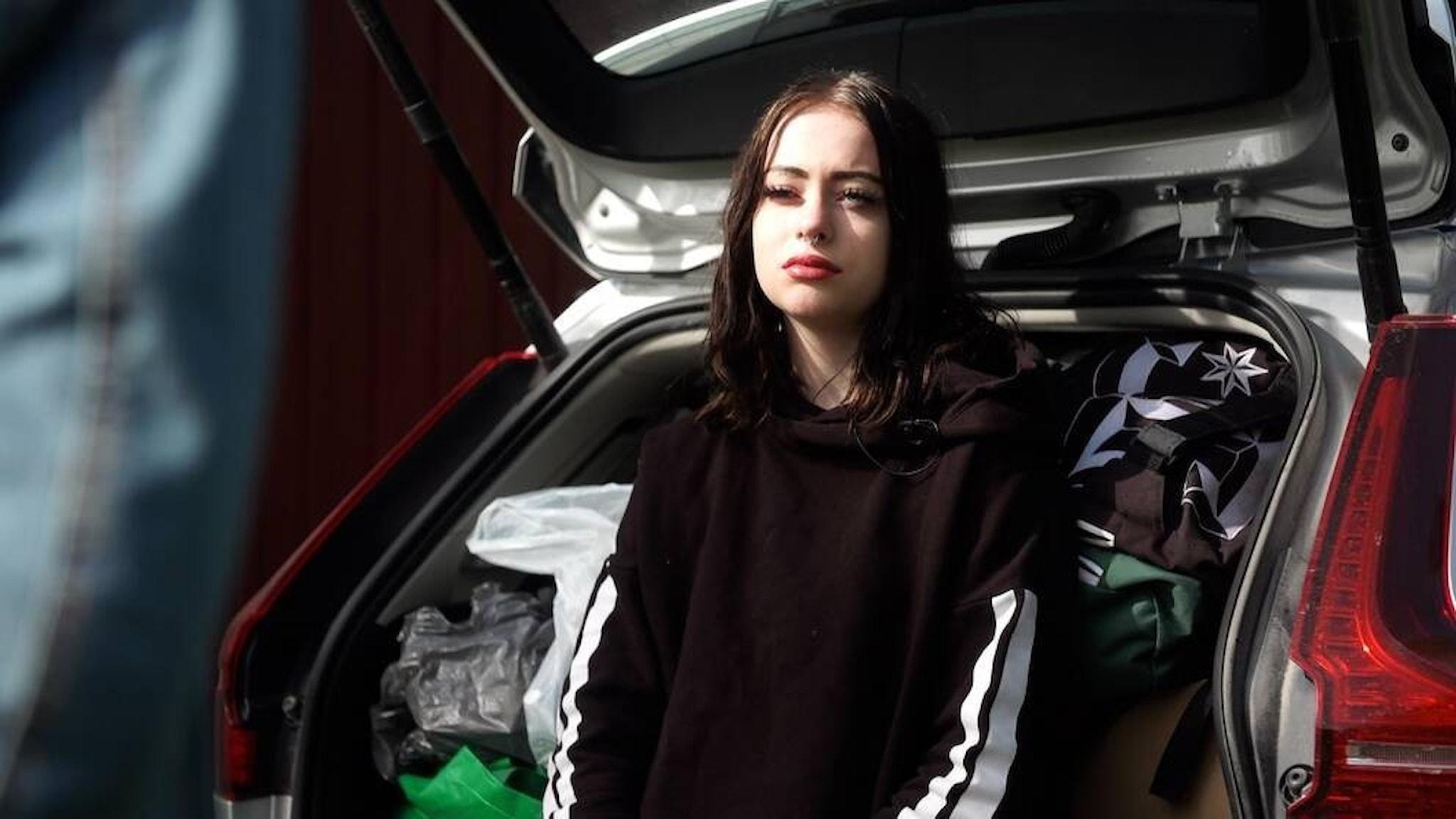 Juni står lutad mot en bil. Hon har långt mörkt hår och en svart tröja.