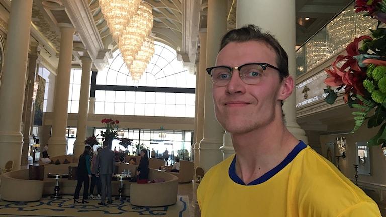 På fotot ser man Isak som är klädd i en T-shirt som är gul och blå. I taket hänger stora kristallkronor och bredvid honom finns en blomsteruppsättning.