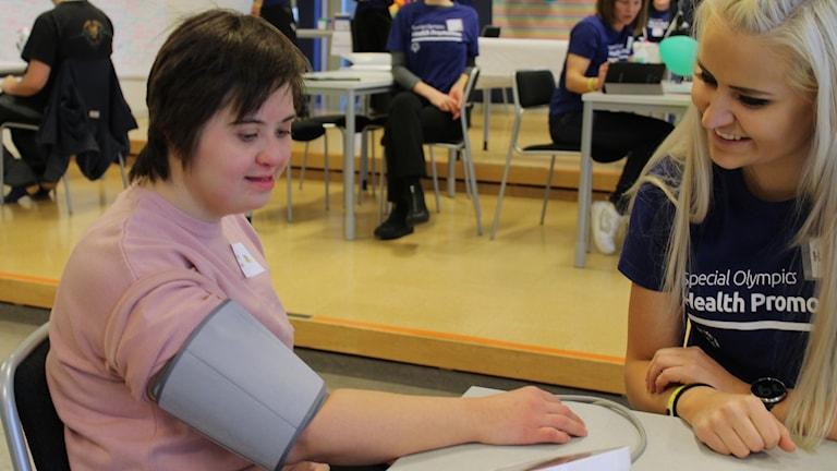 En flicka med intellektuell funktionsnedsättning får blodtrycket taget.