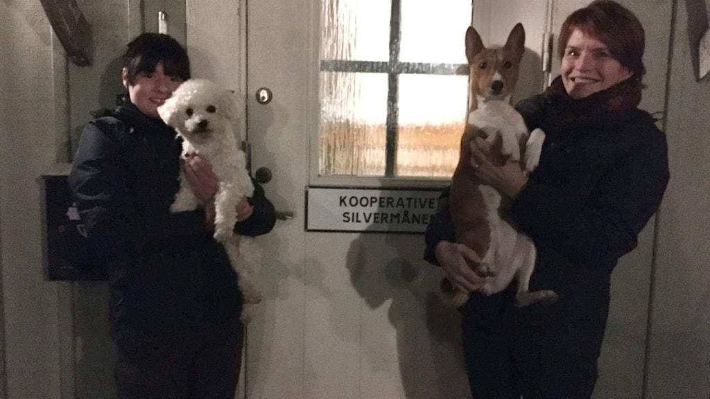 Alma Turén och föreståndaren Sofi Niord står och håller två hundar utanför hunddagiset Silvermånen.