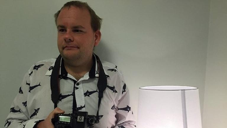 På fotot håller Christian i en kamera och han har en skjorta med hajar på.
