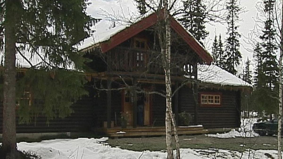 Foto av Fjällbyns gymnasieskola, ett mörkbrunt timmerhus i skogen.