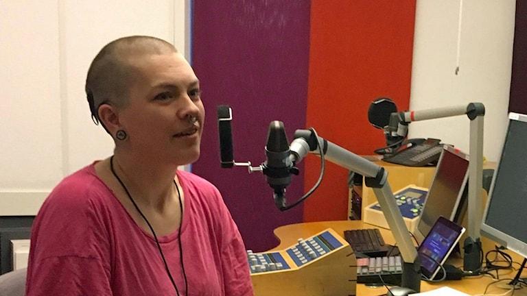 På fotot sitter Frida framför en mikrofon i en radiostudio. Hon har rakat huvud och en rosa tröja.