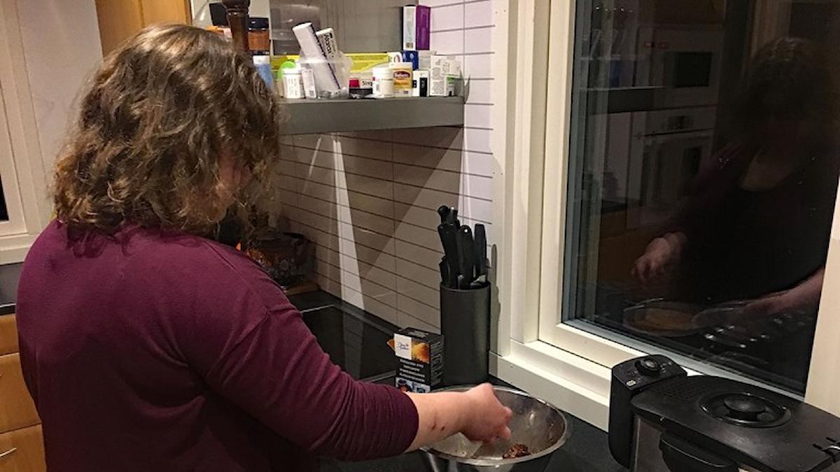 Bilden visar en kvinna som står och lagar mat i ett kök. Bilden är tagen bakifrån så ansiktet syns inte. Hon har mörkt hår och mörklila tröja.