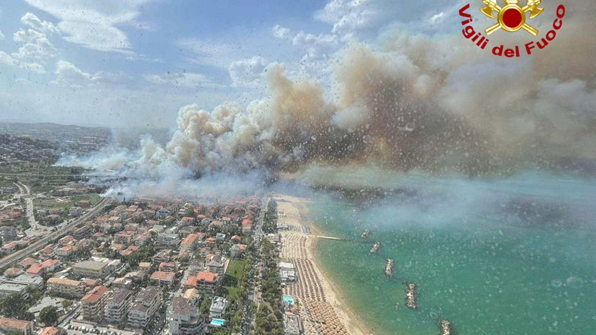 På bilden ser man en italiensk stad till vänster, och havet till höger. Mitt i bilden ser man stora gråa rökmoln.