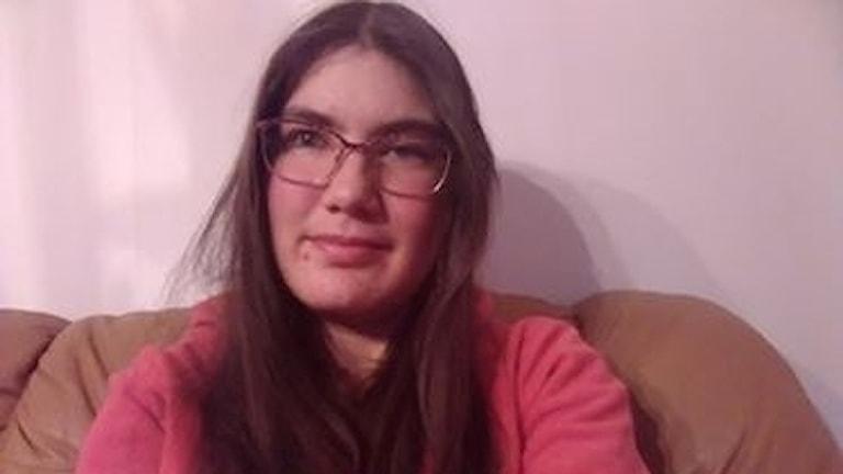 På fotot syns en tjej i rosa tröja  med långt brunt hår och glasögon.