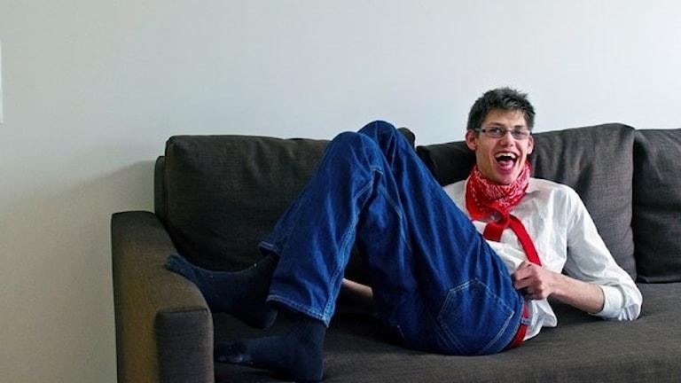Pelle sitter i en soffa och ser glad ut.