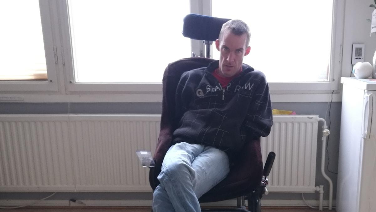 Foto av Markus Petersson. Han har mörkt kort hår och sitter i en rullstol.