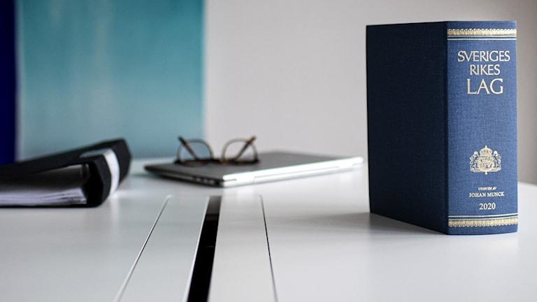 På bilden ser man ett bord med en mycket tjock, blå bok, som är Sveriges lagbok.