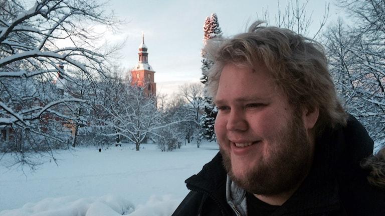 Dan Boberg har skägg och blont hår. Det är snöigt ute och i bakgrunden syns en kyrka.