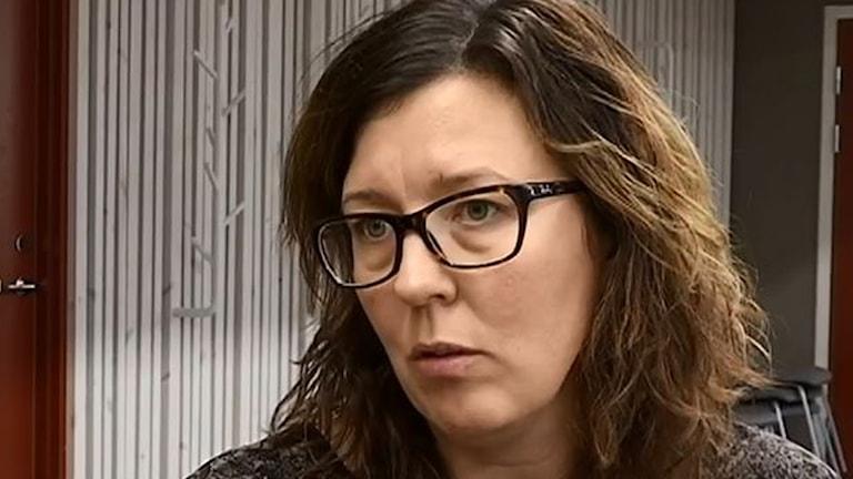 På fotot ser Anna allvarlig ut. Hon har glasögon och långt brunt hår.