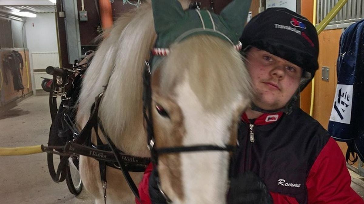 På bilden ser du en ung man med en häst.