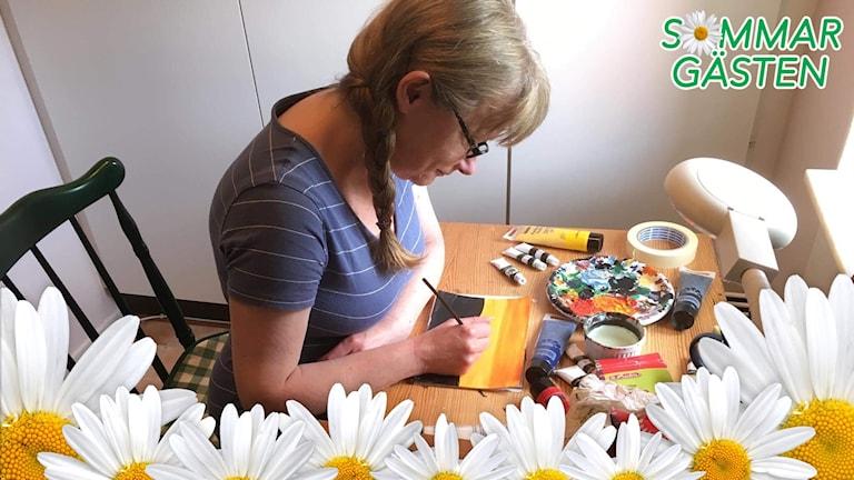 Annika sitter och målar.