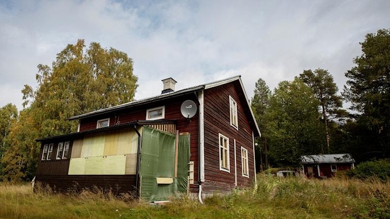 Fotot visar ett rött hus med vita knutar. Flera fönster är igenspikade.