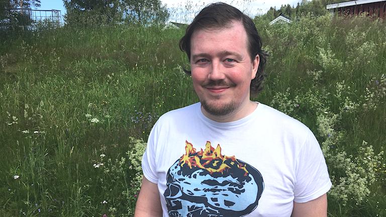 Fotot visar en man med en t-shirt med en döskalle som brinner.