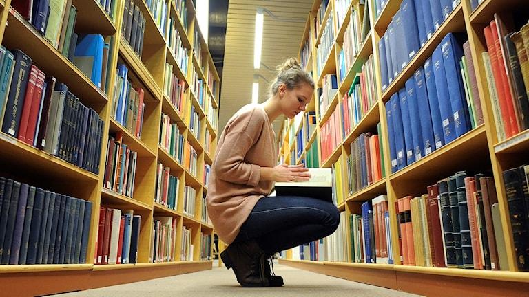 En kvinnlig student sitter på huk i ett bibliotek. Hon har hittat en bok som hon öppnar.