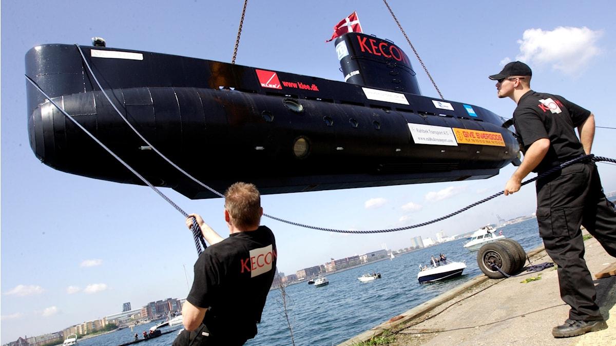 Ubåten är svart. Två män drar i rep när ubåten sänks ner.