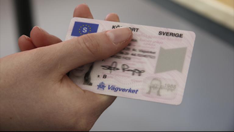 Bilden visar en person som håller i ett körkort.