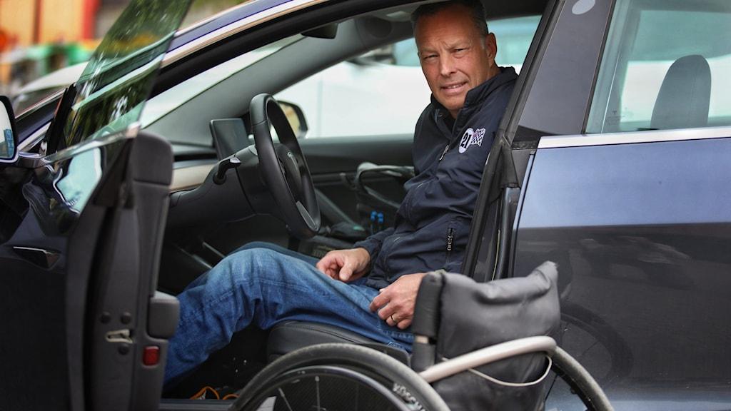 En man sitter i bilen ska ta sig ner i sin rullstol.