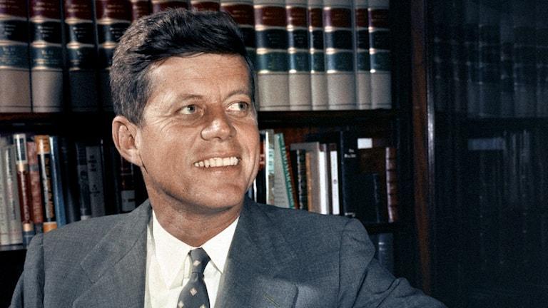 På fotot sitter John F Kennedy framför en bokhylla. Han är klädd i kostym, vit skjorta och slips.