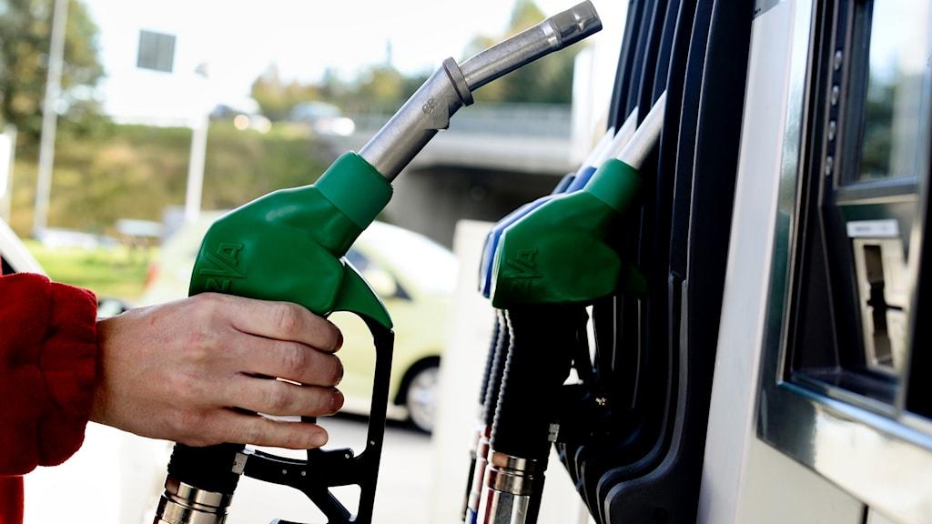 Bilden visar en hand som lyfter ett handtag till en bensinpump.