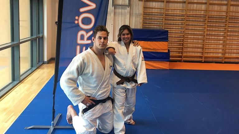 En man i vita judokläder och en flicka i vita judokläder.