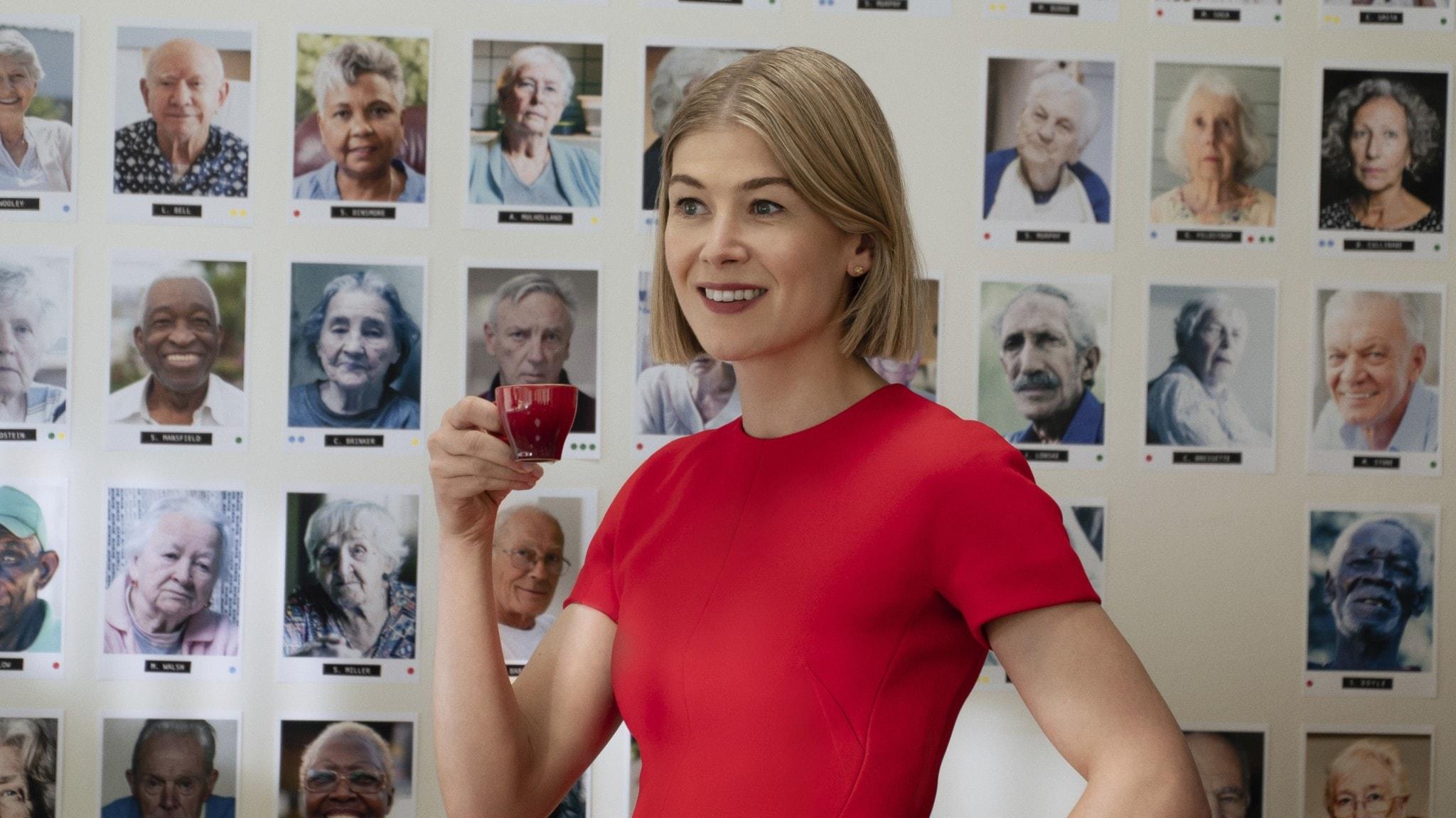 På fotot står Rosamund Pike i en röd klänning och dricker kaffe. Bakom henne syns porträttfoton på en vägg.