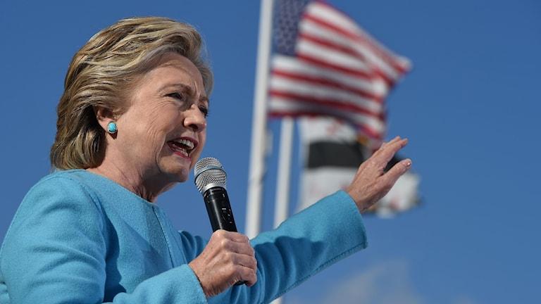 Hon är utomhus. Bakom henne fladdrar en amerikansk flagga.