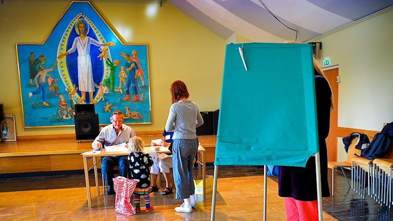En kvinna står bakom en skärm. Längst fram i lokalen finns en stor bild på Jesus.