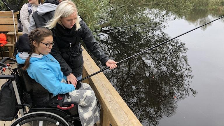 På fotot sitter en tjej i rullstol och metar. Hon får hjälp av en kvinna som står bredvid.