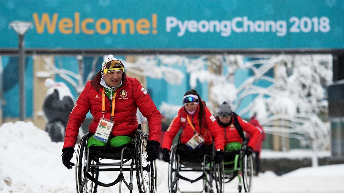 Foto från Paralympics-staden Pyeongchang med några idrottare som kör sina rullstolar under en skylt med texten Välkommen.
