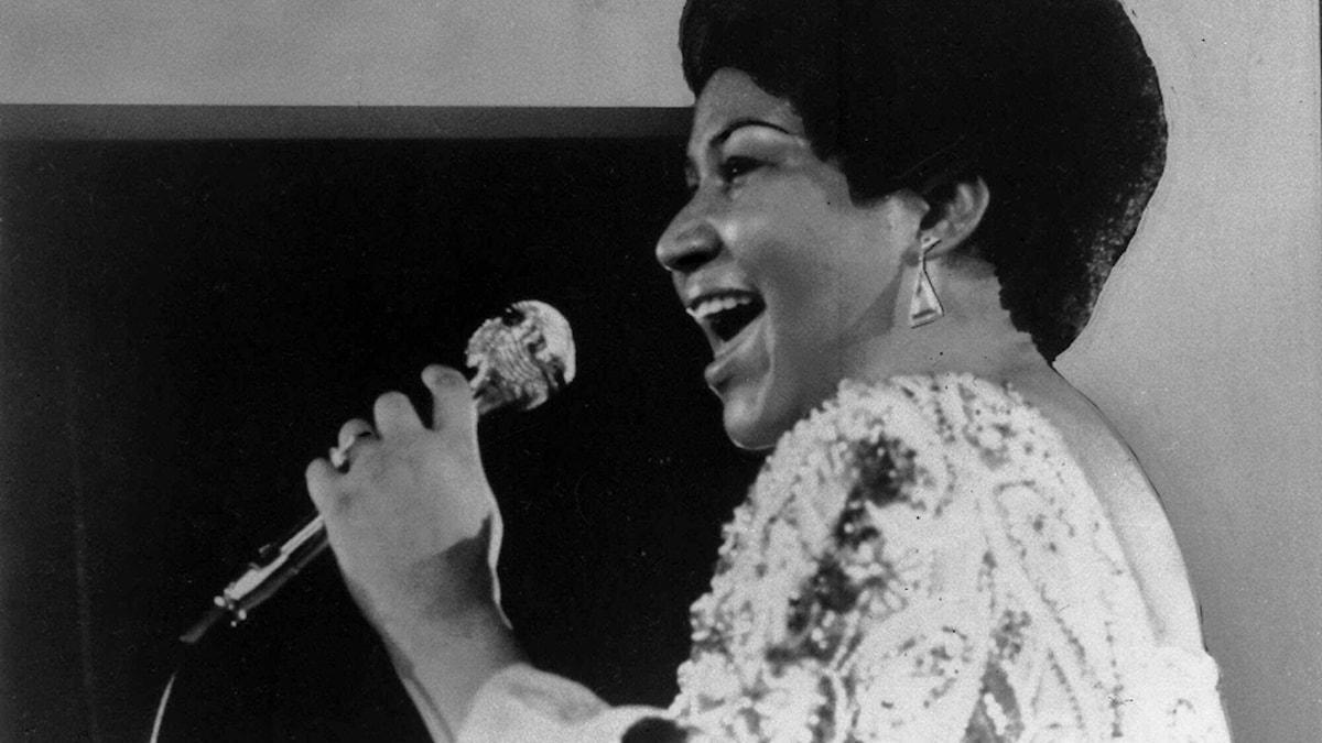 Det är ett svartvitt foto på en kvinna som sjunger i mikrofon. Hon har en afrofrisyr och mörk hudfärg.