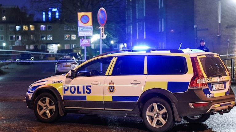 På fotot syns en polisbil och en avspärrning med vita plastband.