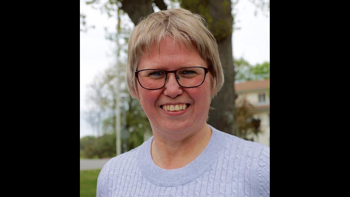 Bilden visar en kvinna som ler med glasögon. Hon står utomhus framför ett träd, har en grå tröja på sig.