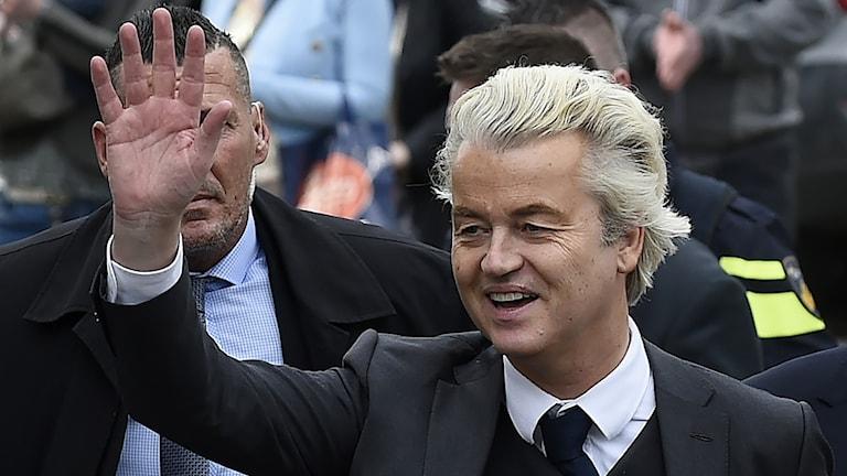 Geert Wilders har ett ljust bakåtkammat hår. Han vinkar till folket. Bredvid honom står vakter.