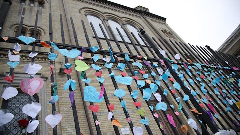 Fotot visar pappershjärtan som fästs på grindarna till synagogan i Göteborg efter attacken i lördags.