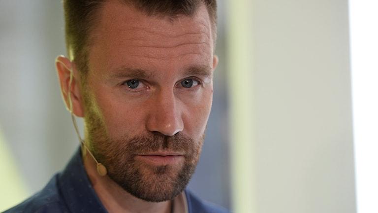Johan är kortklippt och har ett kort rimmat skägg.