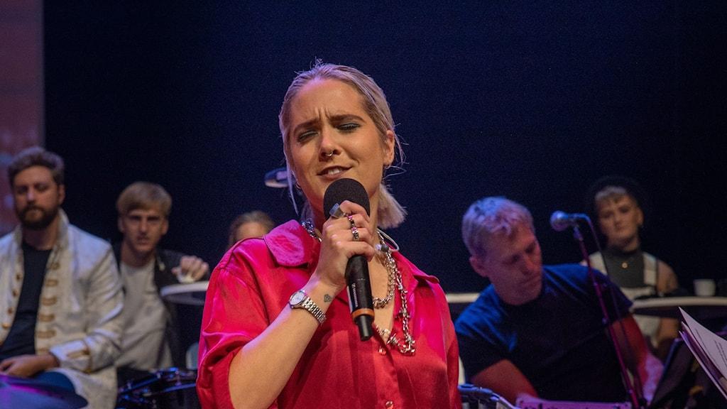 På bilden ser man en kvinna i röd skjorta som sjunger i en mikrofon. Bakom henne syns publik och musiker.